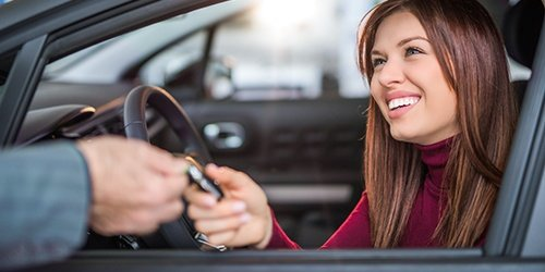 Smiling woman accepting keys at a dealership. Auto Loans available at West Iowa Bank